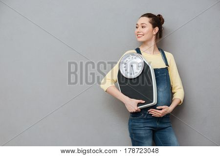 Portrait of a smiling young pregnant woman holding weight scales and looking away at copyspace isolated over gray background