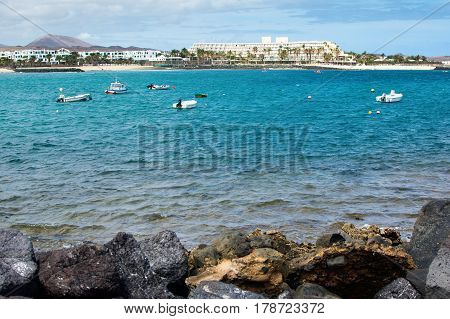 View of Playa de las Cucharas beach in Costa Teguise, Lanzarote, Spain, boats in the ocean, selective focus