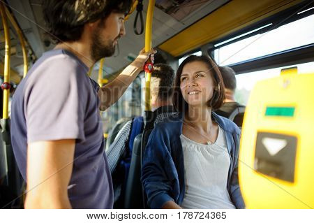Young couple in inside of the city bus. The girl sits the fellow stands nearby. Young people look at each other and smile.