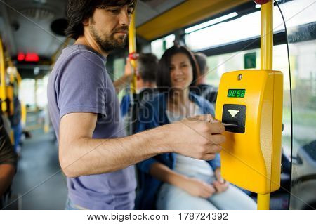Young couple in inside of the city bus. The girl sits and transfers to the guy tickets. The young man inserts the ticket into the validator.