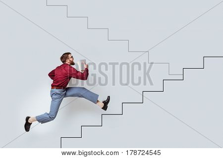 Young bearded man with books running up a drawn stairs along a concrete wall