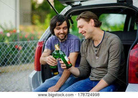 Two young men drink beer from bottles. They have conveniently settled down in an open luggage carrier of the car. Friends derive pleasure from beer and communication.