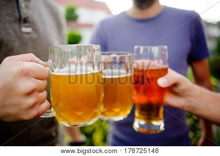 Three young men cheerfully spend time behind a glass of beer. Friends drink beer and in the fresh air and carry on a pleasant conversation.