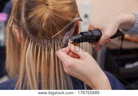 The hairdresser does hair extensions to a young girl a blonde in a beauty salon. Professional hair care.