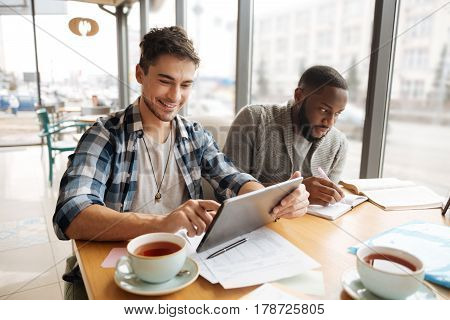 Everyone is busy. Young handsome man is using laptop while his fellow student is taking notes at cafe.