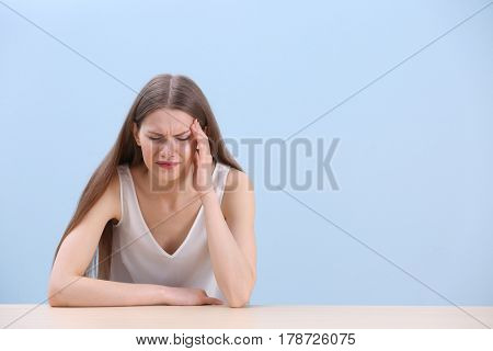 Beautiful young woman suffering from headache while sitting at table, on color background