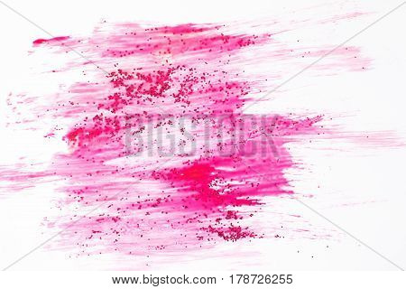 Creative abstract texture background. Smudge fuchsia color paint with pink sparkle glitter on white backdrop. Modern art, feminity concept