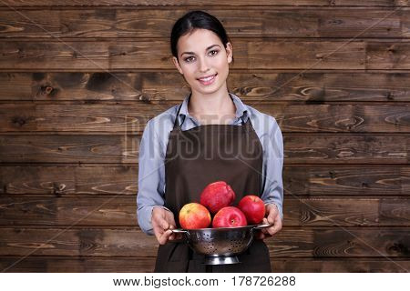 Young woman in apron holding colander with juicy apples on wooden background