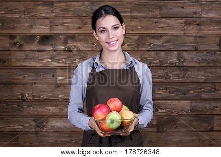 Young woman in apron holding glass bowl with juicy apples on wooden background