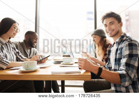 Happy with friends. Nice smiling guy is sitting at cafe surrounded by his friend busy with studying.
