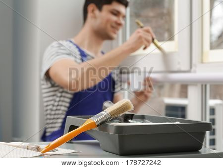 Set of tools for painting and blurred young worker on background