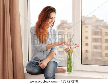 Beautiful young woman with bouquet of flowers sitting on window sill at home