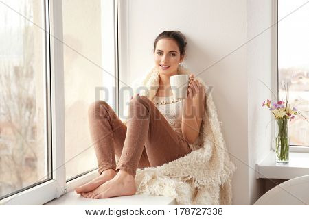 Beautiful young woman drinking coffee while sitting on window sill at home