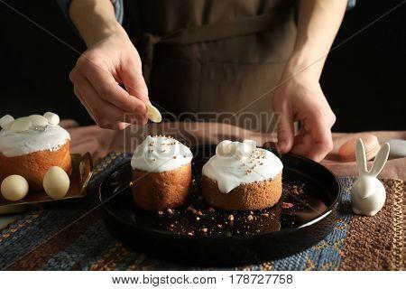 Woman decorating Easter cakes, closeup