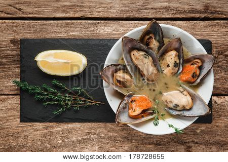 Delicious boiled mussels served with cream sauce on black slate with herbs and lemon, flat lay. Seafood, luxury restaurant menu photo.