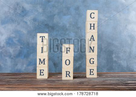 Cubes with text TIME FOR CHANGE on table against color wall