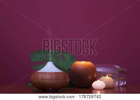 Aroma oil diffuser and candles on blurred color background