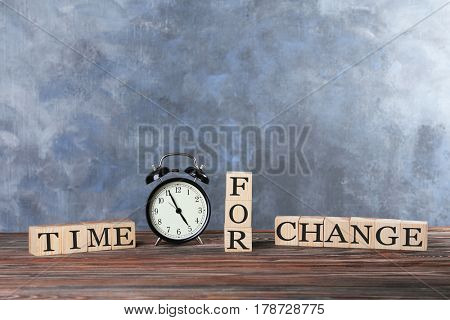 Cubes with text TIME FOR CHANGE and retro alarm clock on table against color wall