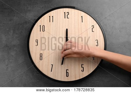 Female hand change time on big wall clock