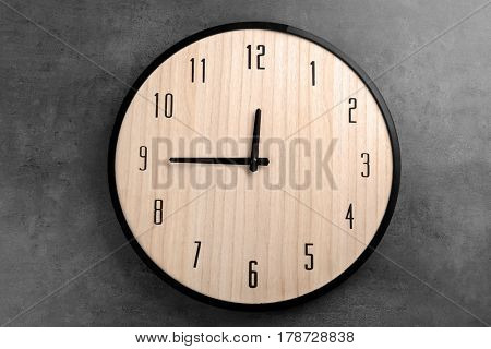 Big clock hanging on dark wall