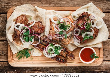 Mixed grilled meat on wood board. Assorted delicious grilled meat served on pita bread with herbs, onion, and tomato sauce, top view. Menu photo.