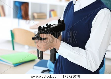 Closeup of schoolboy holding machine gun in classroom