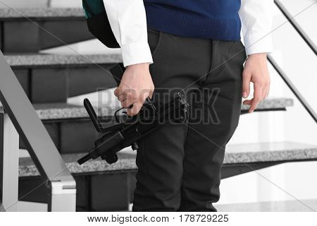 Schoolboy with machine gun in hand standing on stairs