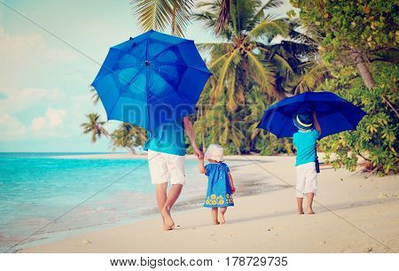 Father and two kids at beach with umbrellas to hide from sun
