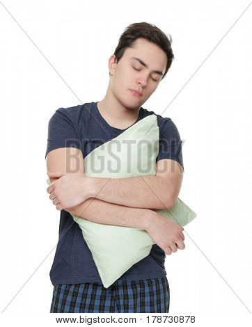 Young sleepy man with pillow on white background
