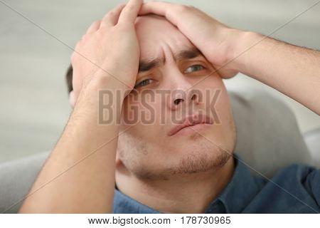 Handsome depressed man at home, closeup