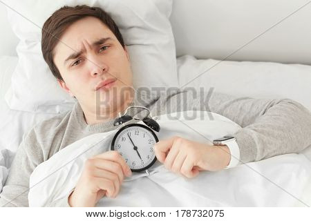 Young man with alarm clock lying in bed at home
