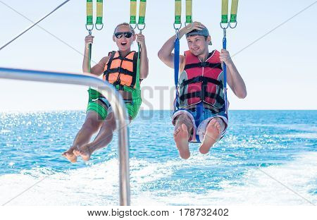 Happy couple Parasailing in Dominicana beach in summer. Couple under parachute hanging mid air. Having fun. Tropical Paradise. Positive human emotions feelings joy. poster