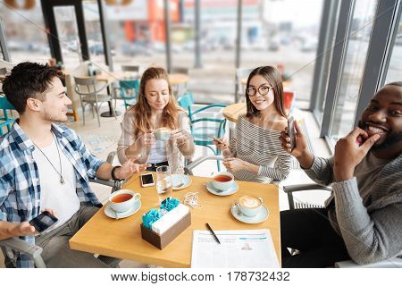 Everybody is involved. Nice group of youngsters posing to camera at cafe while having conversation.