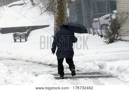BRONX NEW YORK - MARCH 14: Man walks with umbrella during snow storm. Taken March 14 2017 in New York.