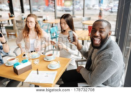 Very emotional. Young handsome guy is expressing happiness surrounded by his friends at cafeteria.