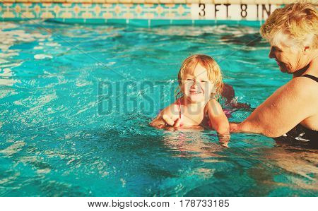 grandmother teaching little granddaughter to swim, active family