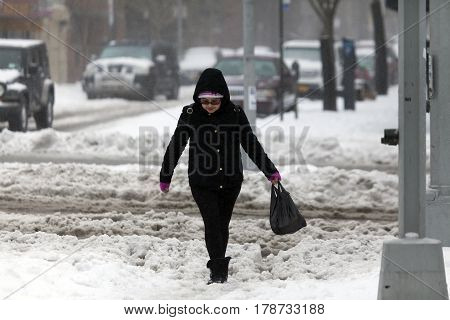 BRONX NEW YORK - MARCH 14: Lady walking along street in snow storm. Taken March 14 2017 in New York.