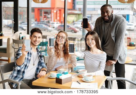 Our best helpmates. Happy international youngsters are showing off their modern smartphones while sitting at cafe.