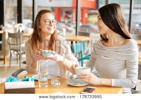 Two besties. Couple of girlfriends are looking at each other while sitting at cafe and holding cups with coffee.