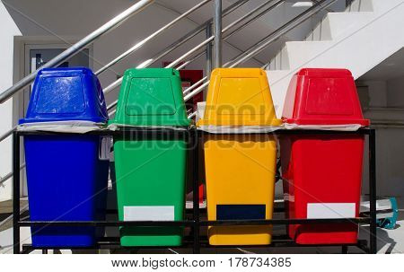 blue, green, yellow and red plastic recycle bin on the floor, colorful, save world concept.