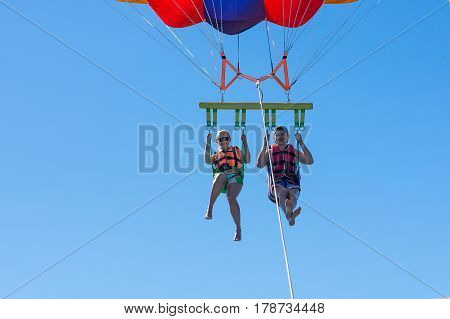 Happy couple Parasailing in Dominicana beach in summer. Couple under parachute hanging mid air. Having fun. Tropical Paradise. Positive human emotions, feelings, joy. poster