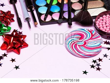 Holiday youth party makeup products with brushes, lollipop, confetti and gift wrap bows. Selective focus, copy space