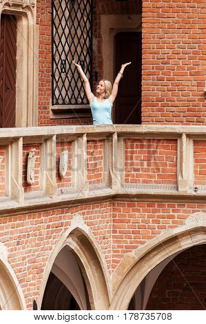Beautiful young woman stands against the background of the ancient university building in Krakow. Poland. Studying abroad. Student life. The ancient universities of Europe