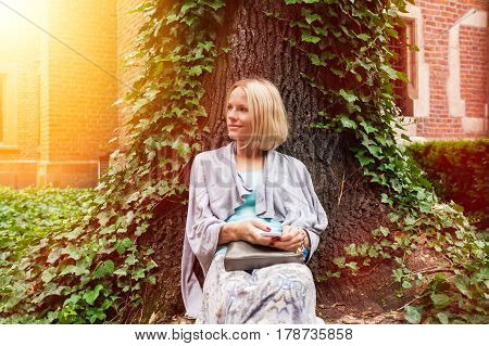Beautiful young woman sitting leaning on a tree in the middle of ivy on a background of the ancient university building in Krakow. Poland. Studying abroad. Student life. The ancient universities of Europe