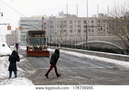 BRONX NEW YORK - MARCH 14: People cross street as sanitation truck plows snow in the Bronx. Taken March 14 2017 in New York.