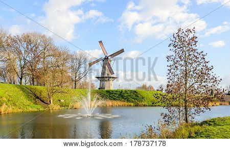 Octagonal grain mill Nooit Gedagt with sails on the edge of the Dutch fortress town Woudrichem in the province of North Brabant. It is a sunny day in the fall season now.