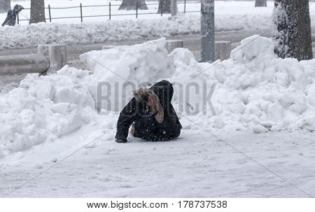 BRONX NEW YORK - MARCH 14: Young boy struggles after falling during snow storm. Taken March 14 2017 in New York.