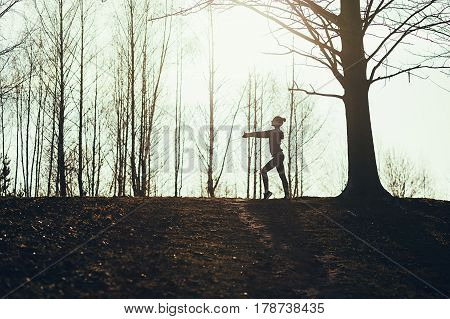Silhouette of woman doing exercise at sunset in summer park