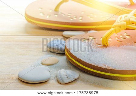 Summer vacations, flip flops on wood deck, sand and pebbles close up