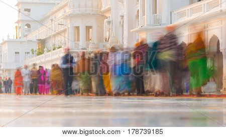 Tourists and worshipper walking inside the Golden Temple complex at Amritsar Punjab India the most sacred icon and worship place of Sikh religion. Blurred motion long exposure.